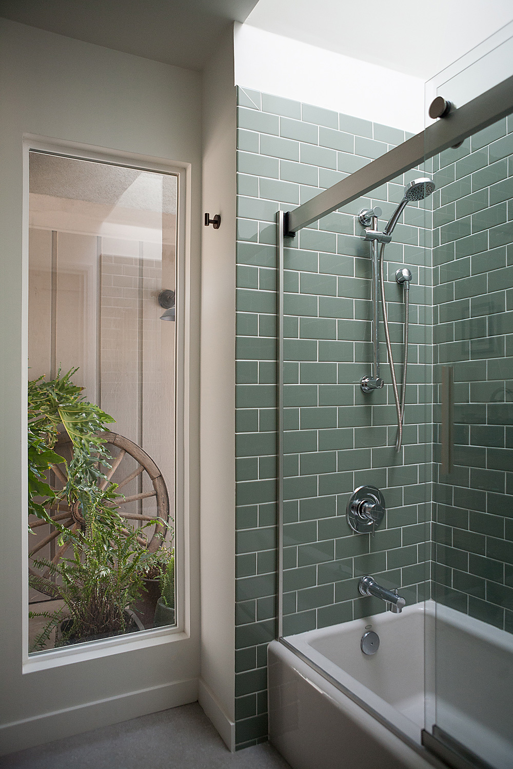 Remodeled bathroom with a natural color palette and views of a private plant atrium give calem & relaxation to your vacation home stay at the Kern River House.