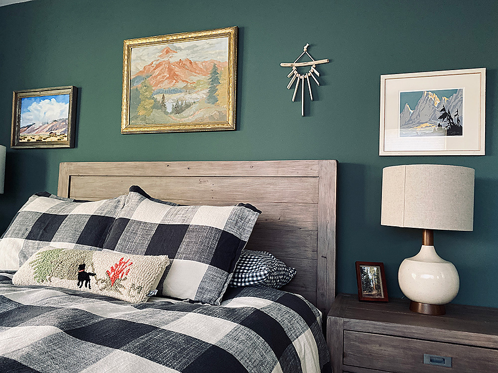 Curated landscape art, rustic bedroom furniture, and cozy bedding are thoughtful interior design elements for the riverfront Big View House in Kern ville, California.